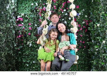 Father and mother with baby and little daughter sit on swing near verdant hedge.