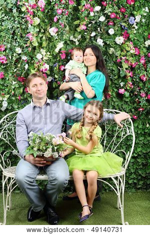 Smiling family of four sit on white bench with bunch of flowers and stand behind in garden near verdant hedge.