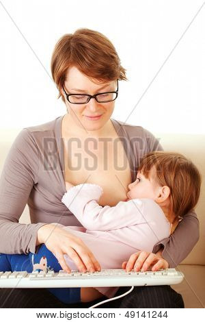 Young woman breastfeeds her baby and typing on the keyboard