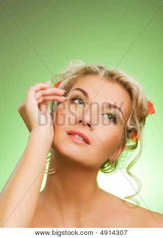 Beautiful Young Woman With Fresh Flowers In Her Hair Looking Up. Spring Concept.