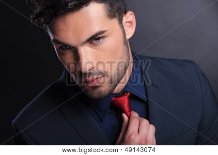 closeup of a young business man fixing his tie while looking at the camera. on a black background