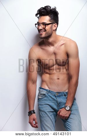 young topless man holding a hand on his crotch while looking away from the camera and smiling. on light gray background