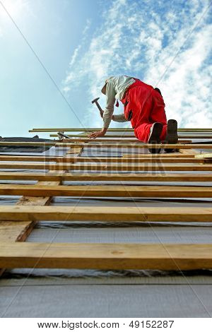 Construction Worker With A Hammer On The Roof