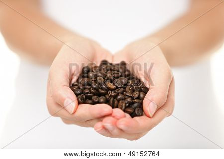 Coffee beans - woman showing medium roasted coffee beans handful. Close up of woman holding coffee beans in hands.