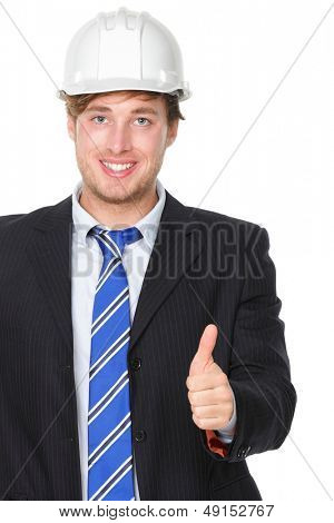 Engineer or architect in suit showing successful thumbs up. Male business man wearing white hard hat signalling success hand sign smiling happy. Portrait of male engineer isolated on white background.