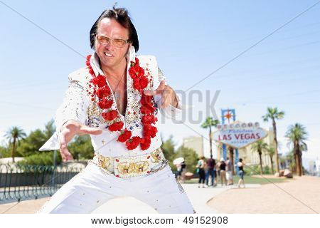 Elvis impersonator man dancing by in front of Welcome to Fabulous Las Vegas sign on the strip. People having fun and Viva Las Vegas concept image with Elvis look-alike doing some crazy moves.
