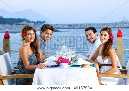 Two Happy Couples Having Dinner At The Seaside