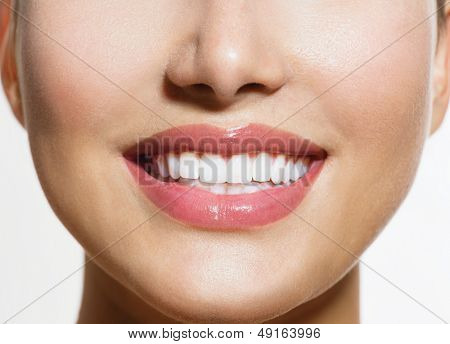 Healthy Smile. Teeth Whitening. Beautiful Smiling Young Woman. Over White background. Laughing Girl