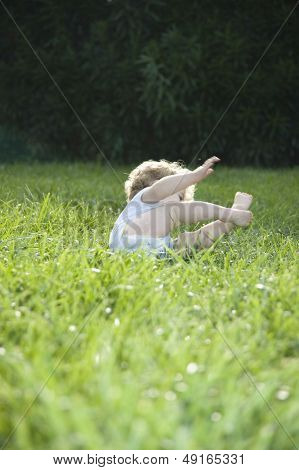 Full length of cute baby girl toppling on grass in lawn