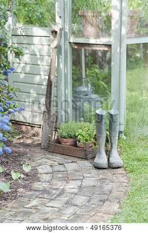 Garden tools and wellington boots outside shed