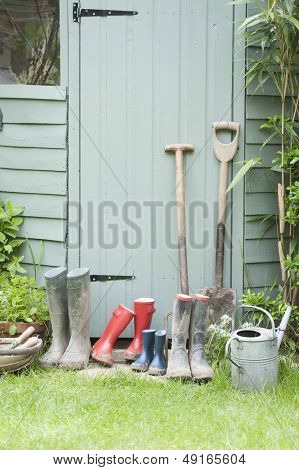 Spades; rake; wellington boots by garden shed