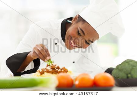 beautiful african female chef garnishing spaghetti dish