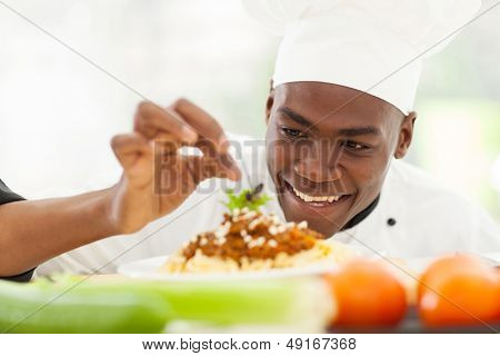 portrait of Afro American chef in restaurant kitchen garnishing pasta dish