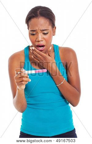 portrait of shocked african woman looking at pregnancy test