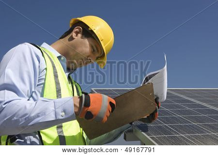 Side view of young maintenance worker looking at clipboard near solar panels