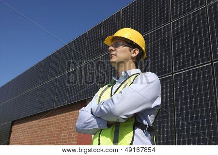 Confident maintenance worker near solar panels