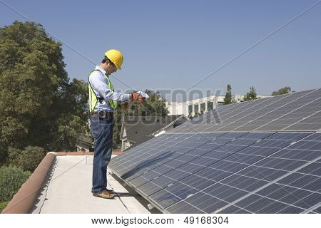 Full length side view of young maintenance worker inspecting solar panels on rooftop