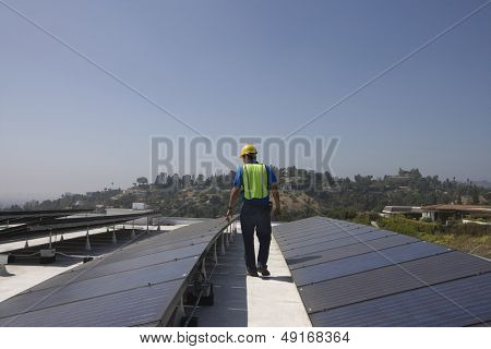 Full length rear view of maintenance worker inspecting solar panels on rooftop