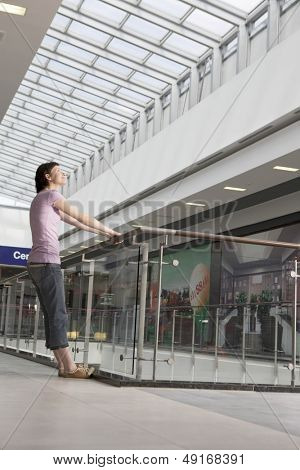 Full length side view of young woman leaning off railing in shopping centre