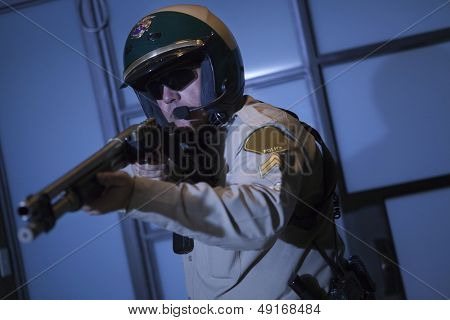 Middle aged traffic cop aiming rifle against door