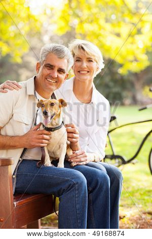 happy senior couple and pet dog at the park