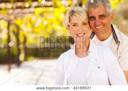 cute mid age couple outdoors looking at the camera
