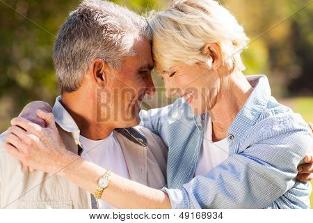 loving middle aged couple hugging with eyes closed closeup portrait