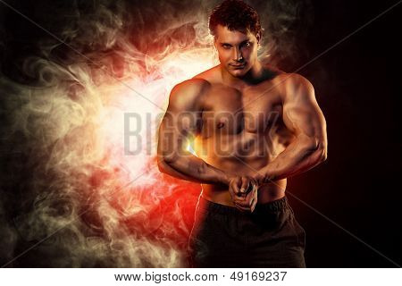 Portrait of a handsome muscular bodybuilder posing over dark background.