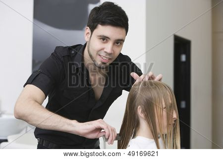 Portrait of male hairstylist combing client's hair at beauty salon