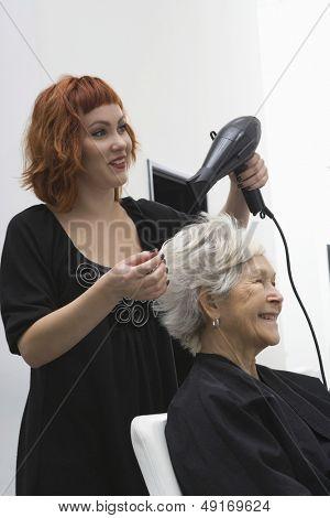 Happy female stylist blow drying senior woman's hair in salon
