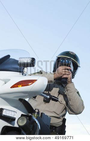 Low angle view of middle aged traffic cop monitoring speed through radar against sky