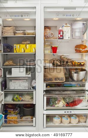 Closeup of open refrigerator with food items in commercial kitchen