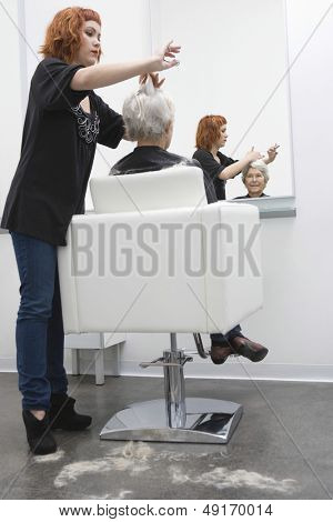 Full length of female hairdresser giving haircut to senior woman in salon