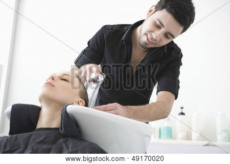 Male hairdresser washing client's hair at beauty parlor