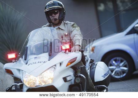 Middle aged traffic cop writing on clipboard while standing by car
