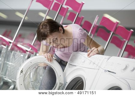 Young woman examining front loader of washing machine in shopping centre