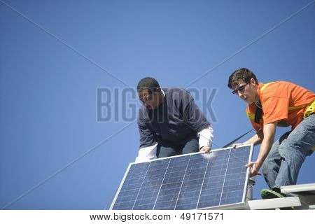 Low angle view of engineers fixing solar panel against blue sky