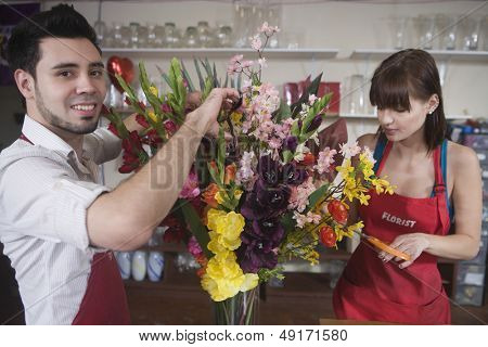 Portrait of male florist working with female colleague in flower shop