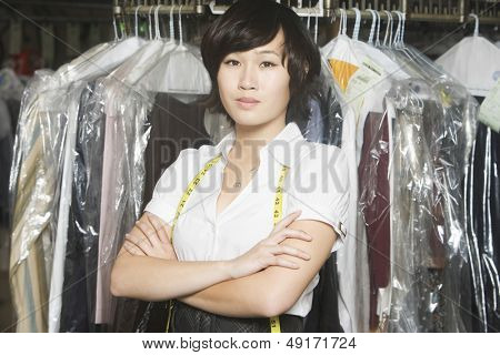 Portrait of confident young woman with arms crossed standing against clothes rail in laundry