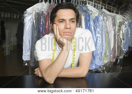 Bored male owner with hand on chin leaning at counter in laundry