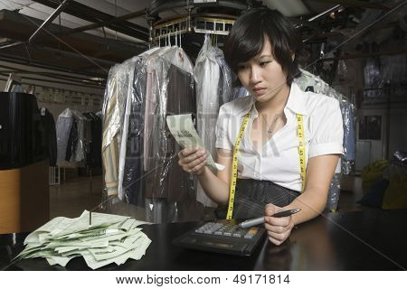 Young woman calculating bills with calculator in laundry