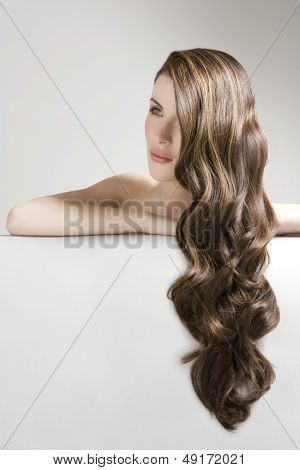 Closeup of a beautiful young woman with long curly brown hair against gray background