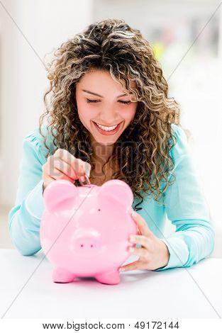 Happy woman putting savings in a piggybank
