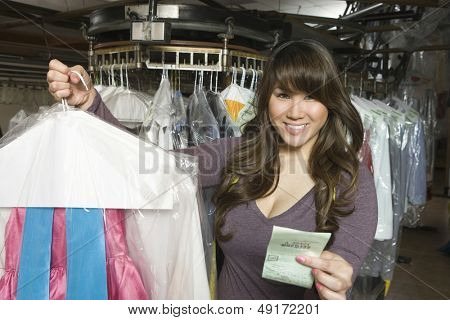 Portrait of happy young woman holding dry cleaned clothes and receipt in laundry
