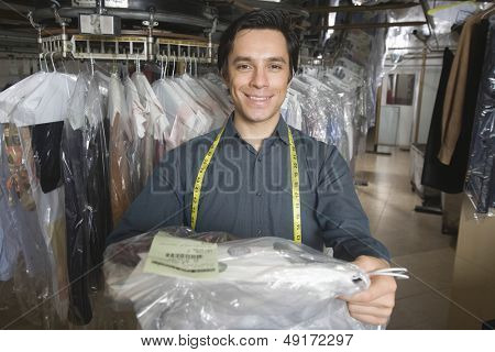 Portrait of confident young owner giving dry cleaned clothes in laundry