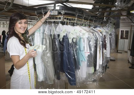 Portrait of young laundry owner with receipt checking clothes
