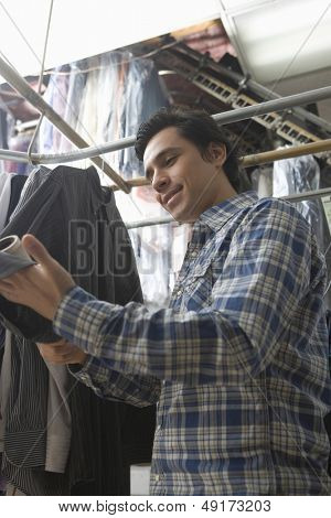 Low angle view of male owner checking clothes in laundry