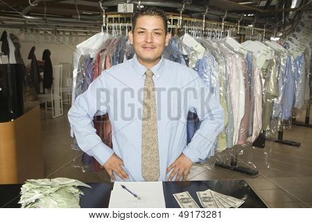 Portrait of confident laundry owner with receipts; notepad and banknotes standing at counter