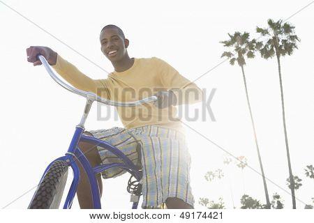 Vista de ángulo bajo de un hombre sonriente con bici en playa
