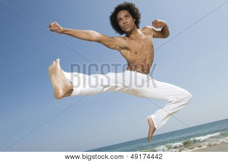 Shirtless young man jumping midair on the beach